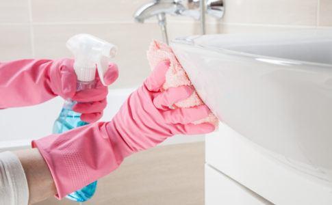 Frau mit Gummihandschuhen putzt das Waschbecken