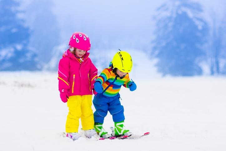 Zwei Kinder üben Ski fahren im Schnee