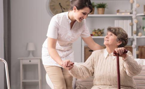 Pflegekraft hilft alter Dame beim Aufstehen