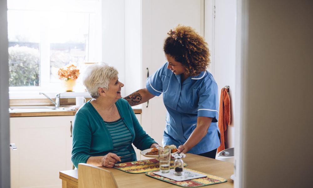 Eine Pflegerin hilft eine alte Dame sich an den Tisch zu setzen.