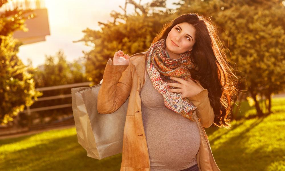 Schwangere Frau steht mit Einkaufstüte vor Bäumen
