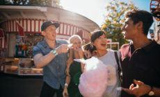 Junge Menschengruppe im Freizeitpark isst Zuckerwatte