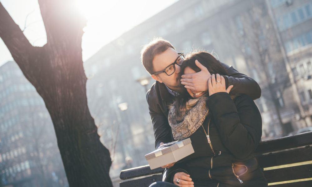 Mann überrascht seine Partnerin mit einem Geschenk im Park