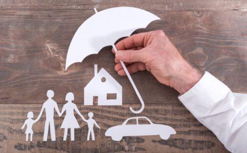 Schirm aus Papier welches eine Familie, ein Haus und ein Auto schützen soll.