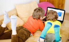 Zwei Kinder liegen auf dem Sofa und gucken auf einen Laptop Bildschirm