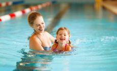 Mutter und Kind üben schwimmen
