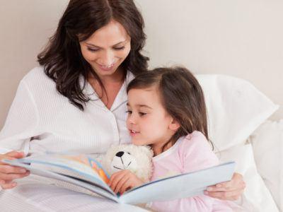 Mutter liest ihrer Tochter aus einem Buch vor