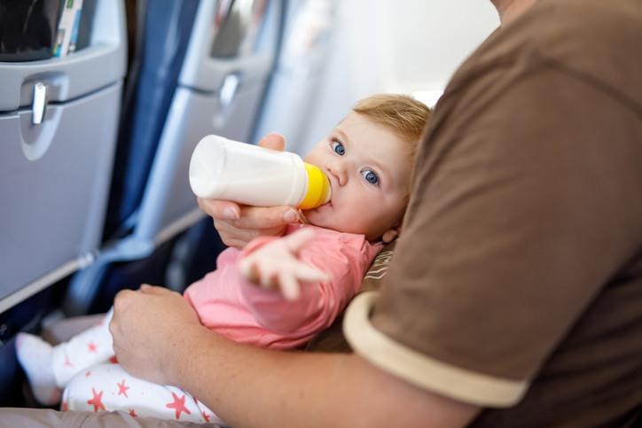 Baby liegt auf Arm im Flugzeug