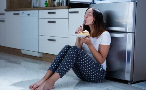 Frau sitzt Nachts vor dem Kühlschrank