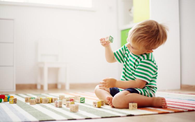 Kind welches auf dem Boden sitzt und spielt
