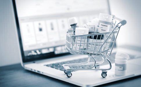 Miniatur-Einkaufswagen mit Medikamenten auf einem geöffneten Laptop