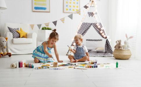 2 Kinder sitzen im Kinderzimmer und spielen miteinander