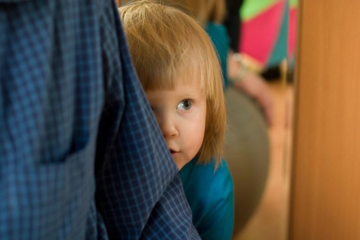 Kind versteckt sich schüchtern hinter Eltern