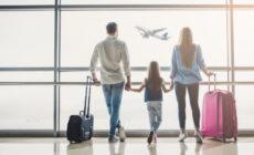 Familie steht am Flughafen vor dem Fenster und schaut sich ein fliegendes Flugzeug an