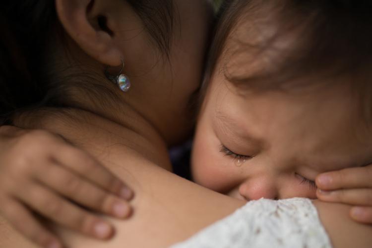 Kind weint auf dem Arm der Mutter