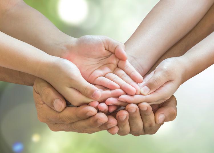 6 Hände die sich die Hand halten