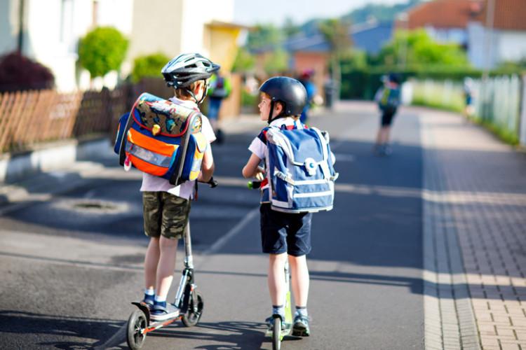 Zwei Kinder auf einem Roller im Straßenverkehr