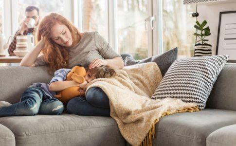 Mutter sitzt auf dem Sofa mit ihrem Kind