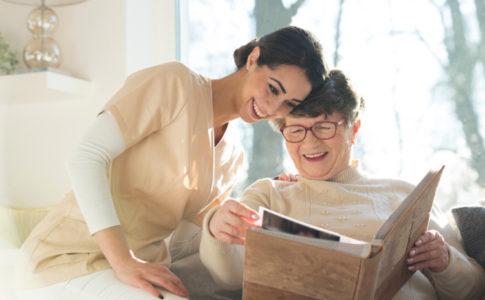 Eine Altenbetreuerin schaut sich ein Album mit einer älteren Dame an