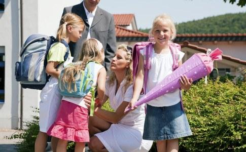 Glückliche Familie bei der Einschulung einer Tochter