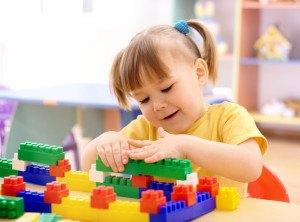 Mädchen spielt mit Lego