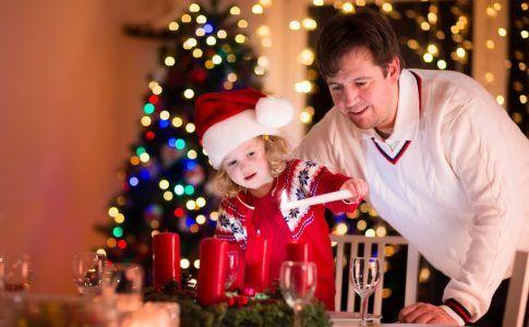 Vater und Tochter entzünden die Kerzen am Adventskranz