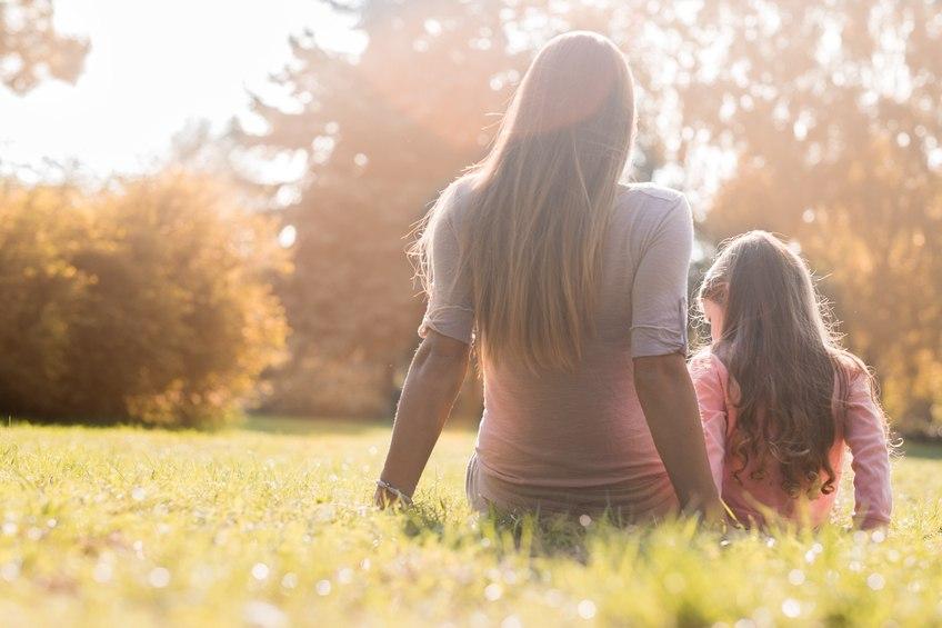 Alleinerziehende Mutter und Kind sitzen auf einer Wiese