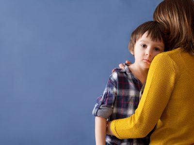 Unterhaltzahlungsbedürftiges Kind schaut über die Schulter der Mutter