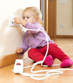 Baby girl playing with electrical extension