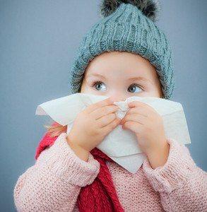 Krankes Kleinkind mit Mütze und Taschentuch