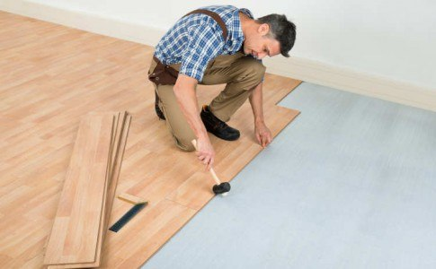 Mann verlegt Laminatfußboden in einer hellen Wohnung