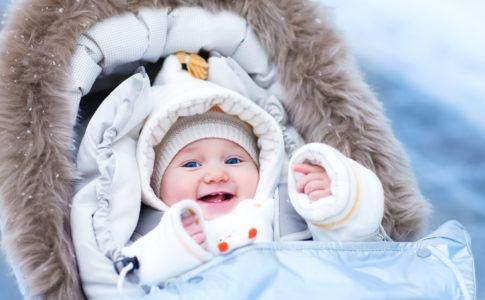 Baby sitzt im Winter warm eingepackt im Kinderwagen und lacht