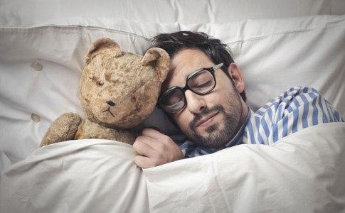 Mann schläft mit Teddy