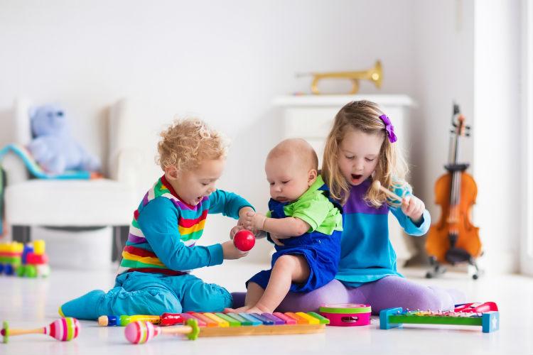 musikalische Früherziehung sinnvoll? - drei Kinder spielen mit Kindermusikinstrumenten