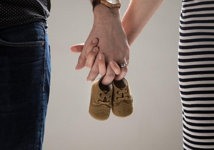 Hände und kleine kinderschuhe