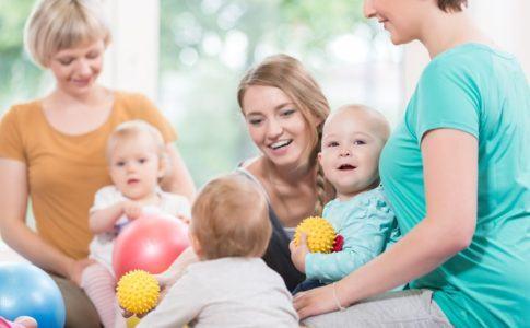 drei kinder spielen mit vier jungen Frauen im sitzen