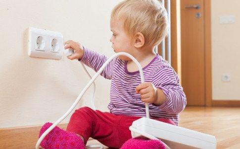 Baby spielt mit Steckdose