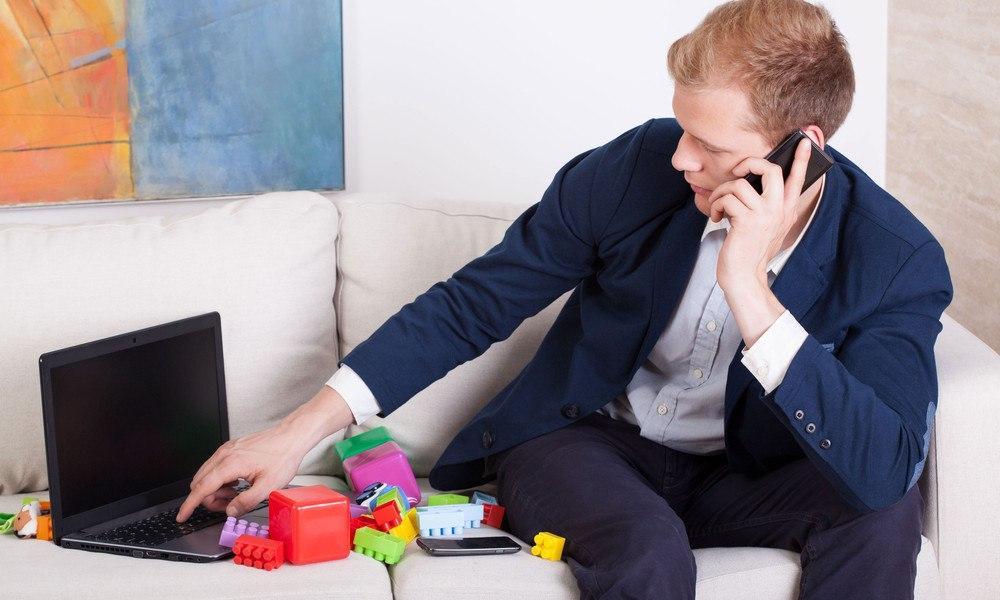 Geschäftsmann sitzt mit Laptop zwischen Spielzeug