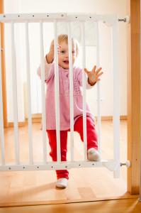 Kleinkind steht vor Absperrung der Treppe