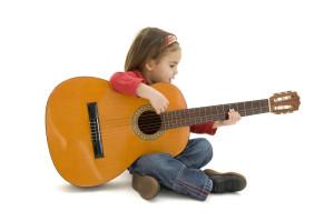 Mädchen sitzt mit Gitarre auf Boden