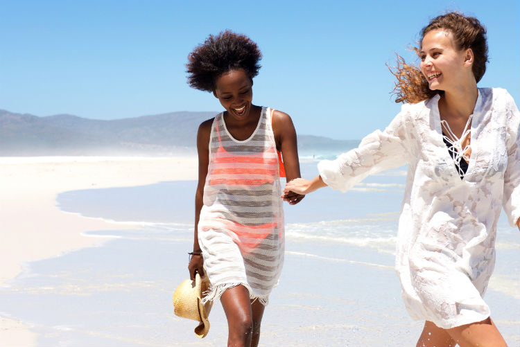 sommerliche mode - zwei Frauen laufen am Strand in Sommerkleidern