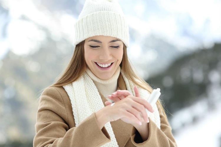 Frau cremt ihre Hände im Winter ein