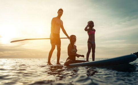Junge Familie beim Stand Up Paddling auf einem See