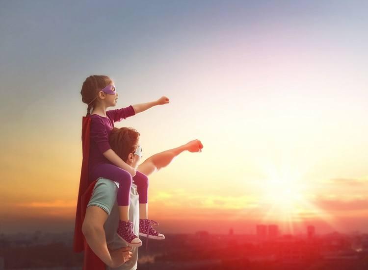Papa trägt Tochter auf Schultern beide im Superhelden Kostüm