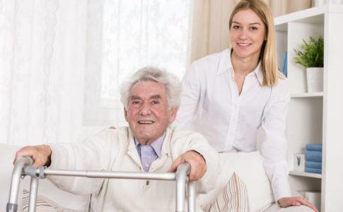 wohnen im alter - alter Mann situt mit Gehhilfe vor sich auf Sofa & junge Frau steht hinter ihm