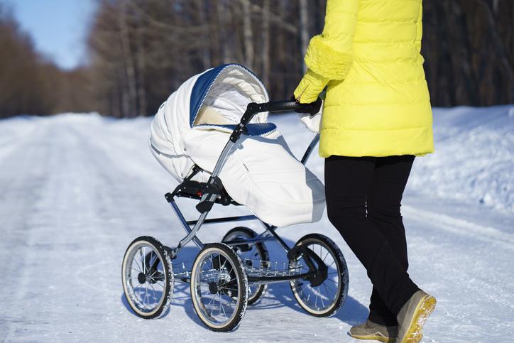 Mutter mit Kinderwagen im Schnee